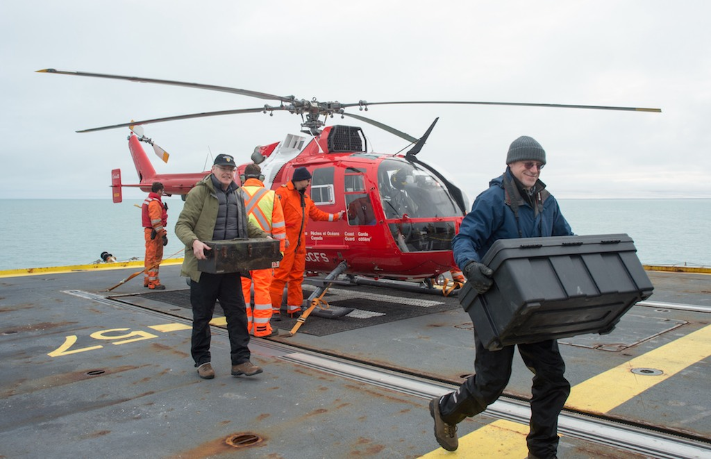 Helicopter landing in Arctic, researchers unloading cargo