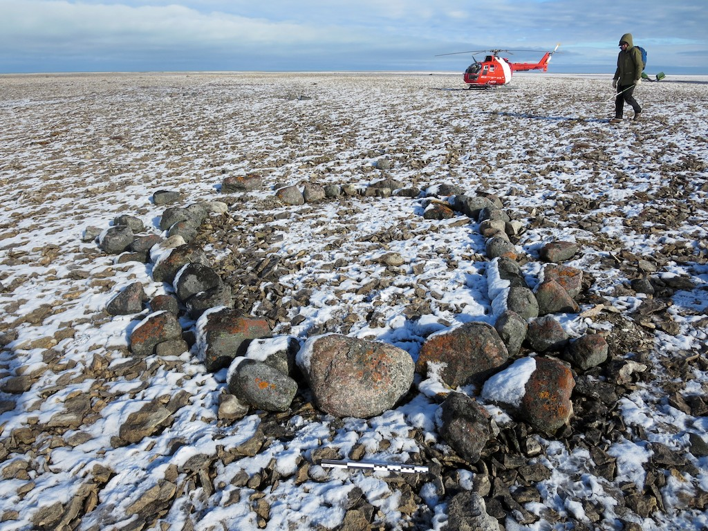 Circle of stones in the Arctic with helicopter in background
