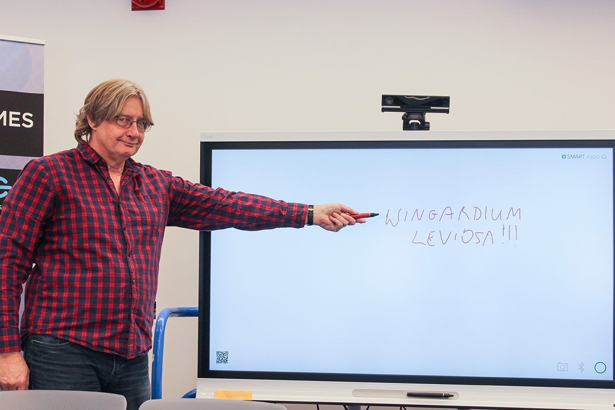 Professor Randall pointing at screen with Harry Potter spell written on it
