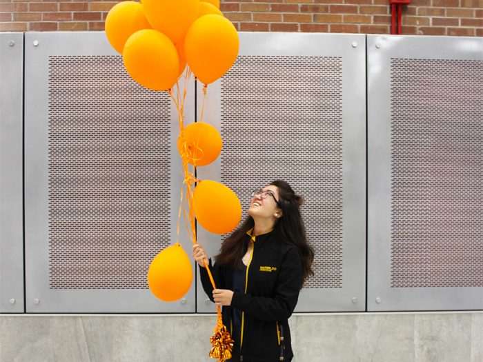 Amy holding orange balloons